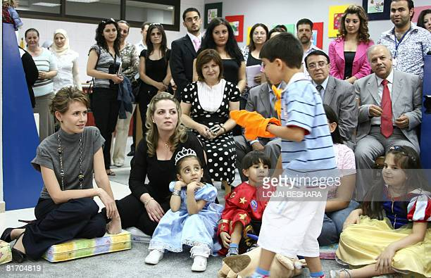 Syrian first lady Asma alAssad watches a spontaneous children puppet show during the opening ceremony of a public library for children in Damascus on...