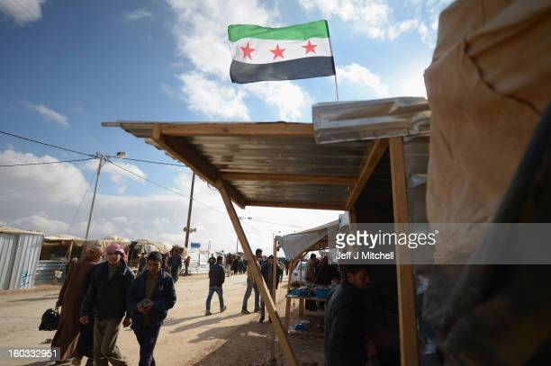 Syrian flag flies over a hut as refugees go about their daily business in the Za'atari refugee camp on January 29 2013 in Mafraq Jordan Record...