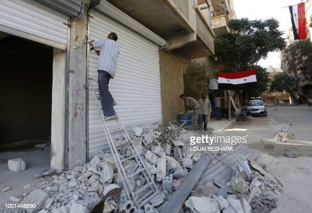 Syrian flags hang from buildings as workers rebuild destroyed stores in Harasta on the outskirt of the Syrian capital Damascus on July 15 2018 After...
