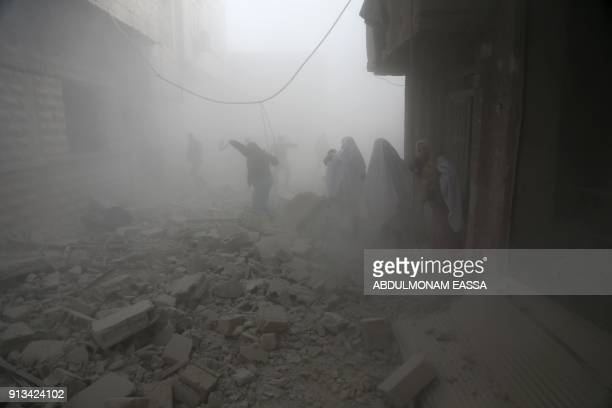 TOPSHOT Syrian flee their homes following an airstrike in the rebelheld besieged town of Arbin in the eastern Ghouta region on the outskirts of the...