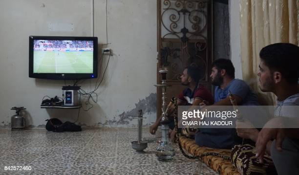 Syrian football fans watch the Portugal vs Hungary World Cup qualifier football match at a friend's house in Binnish on the outskirts of Idlib on...