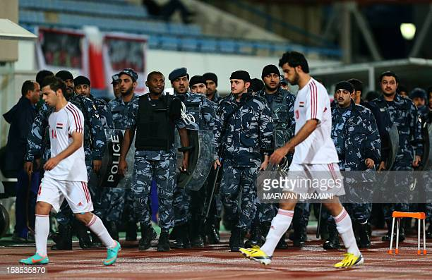 Syrian football players walk in front of Kuwaiti riot police as they arrive at the pitch after several Syrian nationals and opponents to Syria's...