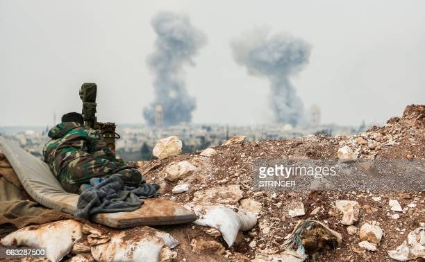 Syrian forces' artillery observer looks through a scope as smoke plumes rise on the horizon near the town of Qumhanah in the countryside of the...