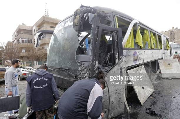 Syrian forensics examine a damaged bus at the scene of a bombing following twin attacks targeting Shiite pilgrims in Damascus' Old City on March 11...