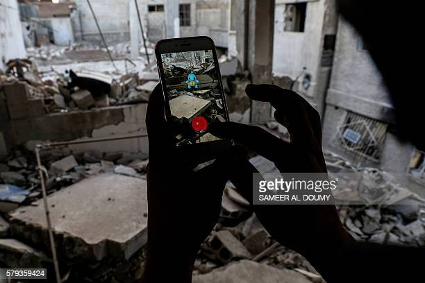 Syrian gamer uses the Pokemon Go application on his mobile to catch a Pokemon amidst the rubble in the besieged rebelcontrolled town of Douma a...