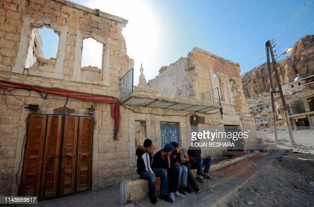 Syrian gather next to a damaged building in the ancient Christian town of Maalula 56 kilometres northeast of the Syrian capital Damascus on May 13...