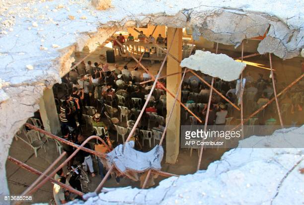 Syrian gather on July 12 2017 at a destroyed building in Khan Sheikhun a rebelheld town in the northwestern Syrian Idlib province 100 days following...