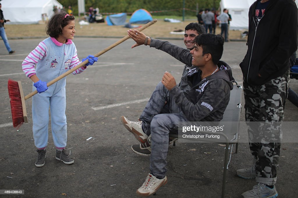 Syrian girl Ahlam Ahmed Mohammed, aged 11, playfully brandishes her broom to encourage other migrants to join in the cleaning up of a holding area just metres across the Hungarian border in the Austrian village of Heiligenkreuz on September 21, 2015 in Heiligenkreuz, Austria. Thousands of migrants have arrived in Austria over the wekend with more en-route from Hungary, Croatia and Slovenia. Politicians across the European Union are to hold meetings on the refugee crisis with EU interior ministers meeting tomorrow and EU leaders attending an extraordinary summit on Wednesday.