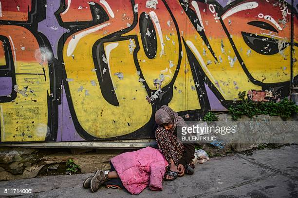 Syrian girl begs in the street as another child sleeps next to her in downtown Istanbul on February 22 2016 / AFP / BULENT KILIC