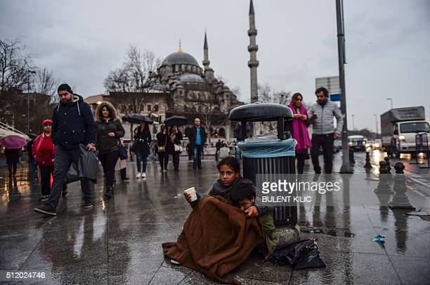 A Syrian girl begs in the street of Istanbul as she hugs another child on February 24 2016 / AFP / BULENT KILIC