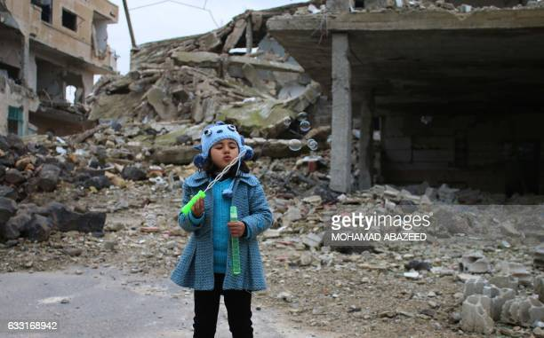 Syrian girl blows bubbles amid the rubble of destroyed buildings in the rebelheld area of Daraa in southern Syria on January 31 2017 / AFP PHOTO /...