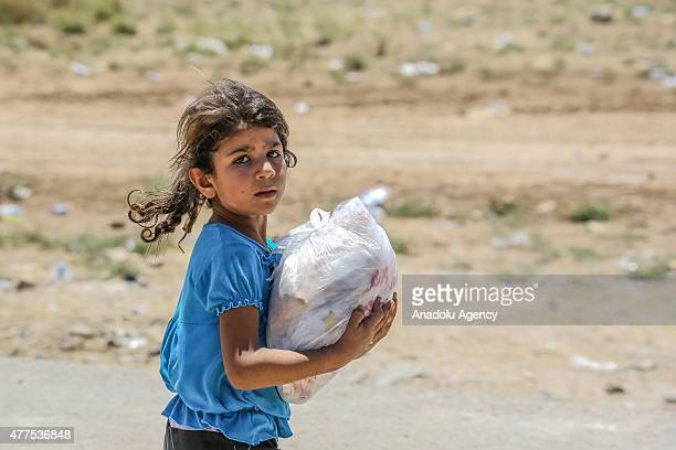 Syrian girl carries a bag of bread distributed by a relief organization as she waits at Akcakale Border gate with her family to return to the Syrian...