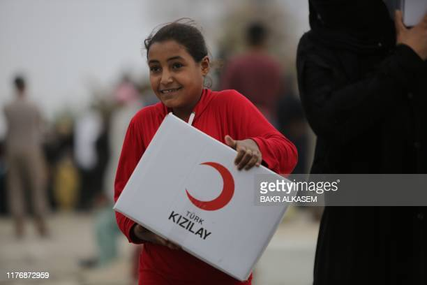 A Syrian girl carries a box of aid distributed by the Turkish Red Crescent on October 19 in the Syrian border town of of Tal Abyad seized by...