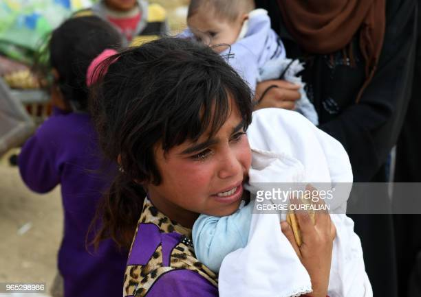 A Syrian girl carries a child while receiving food aid from Russian military personnel after arriving in a convoy carrying displaced people returning...