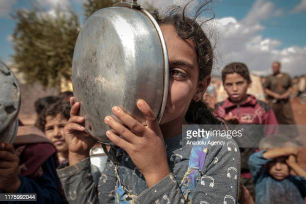 Syrian girl covers her face with a cooking pot as they queue to receive food aid in Idlib Syria on October 07 2019 While more than 820 million people...