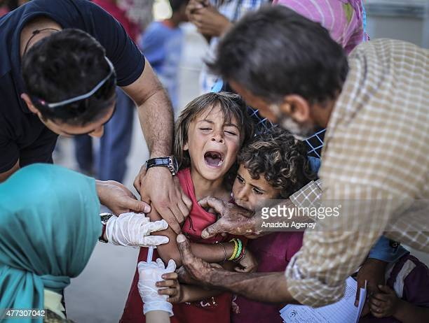 Syrian girl cries as she is vaccinated before crossing into Turkey from Akcakale Border Gate in Sanliurfa Turkey on June 16 2015 Hundreds of Syrians...