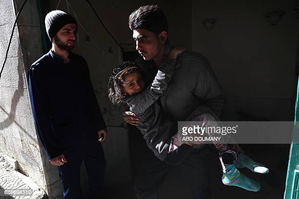 Syrian girl cries as she's carried into a makeshift hospital following a reported government airstrike on the rebelheld town of Douma on the eastern...