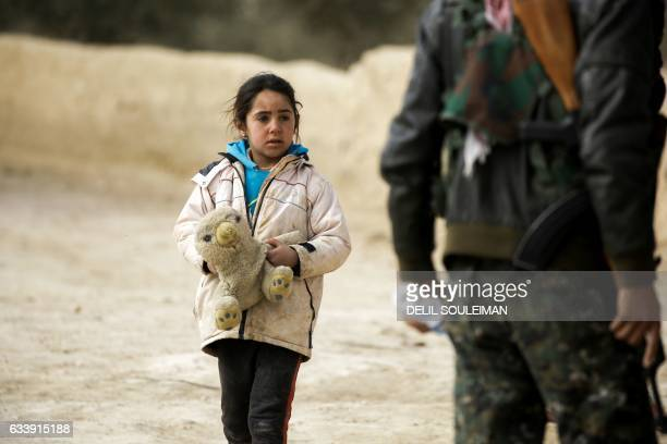 A Syrian girl from Waset Hashm a small village east of Raqa walks past a member of the Syrian Democratic Forces as residents of the town prepare to...