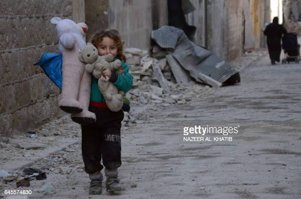 A Syrian girl holding her stuffed toy stands next to the rubble of buildings in the northwestern Syrian border town of alBab on February 25 2017...