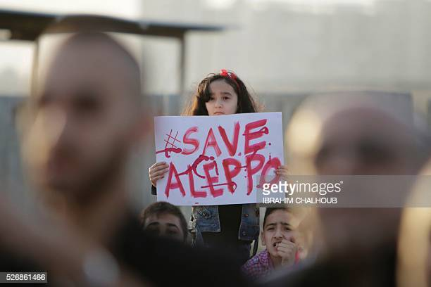 Syrian girl holds a placard during a rally in solidarity with Aleppo in the Lebanese northern port city of Tripoli on May 1 2016 More than a week of...