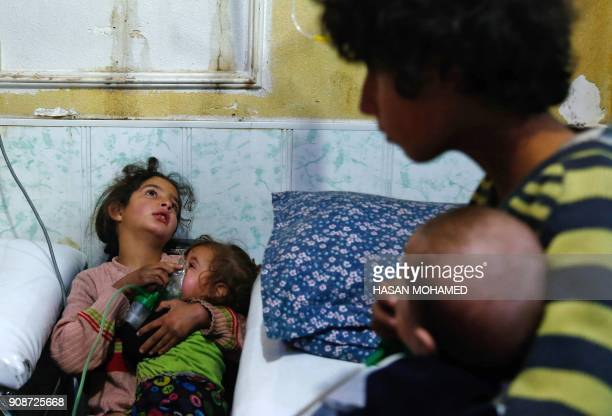 Syrian girl holds an oxygen mask over the face of an infant at a makeshift hospital following a reported gas attack on the rebelheld besieged town of...
