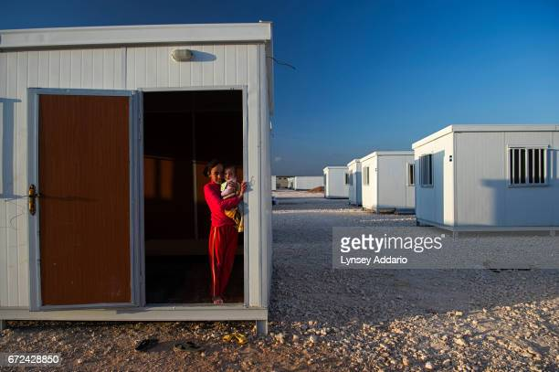 A Syrian girl holds her sister while standing in the door of the trailer alotted to her family earlier that day by the United Nations High Commission...