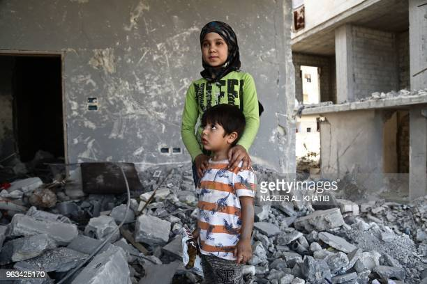 Syrian girl Inas Haymur and her brother Saad pose for a photograph in Afrin on May 26 2018 Displaced from their homes in Syria's Eastern Ghouta...