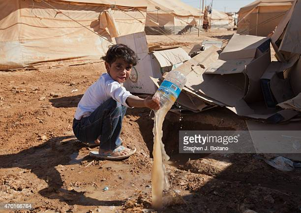 Syrian girl play in dirty water need the collapsed latrine at the Zaatari Refugee Camp in Jordan