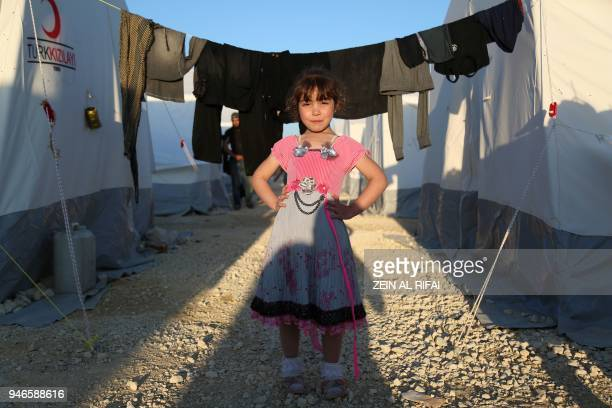 A Syrian girl poses for a photo at a camp for displaced Syrians in alBil east of the rebelheld town of Azaz in northern Syria on April 15 2018 / AFP...