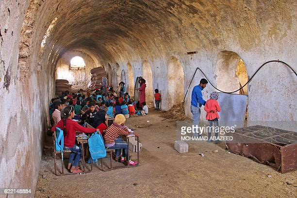 Syrian girl practices basic arithmetic operations with a teacher during class in a barn that has been converted into a makeshift school to teach...