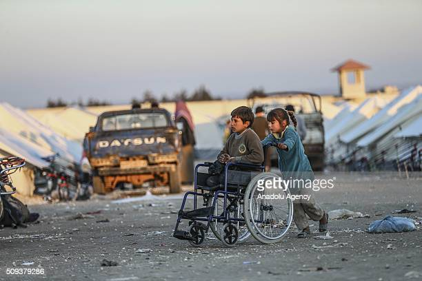 Syrian girl push a wheelchair carrying an amputee boy as they shelter at tents and try to live their lives with humanitarian aid send by Turkey UNHCR...