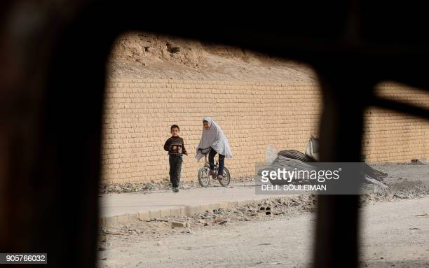 A Syrian girl rides a bicycle next to a boy in the northern Syrian city of Raqa on January 11 2018 after a huge military operation led on the ground...