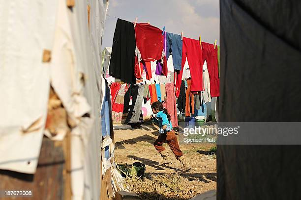 Syrian girl runs through a makeshift refugee camp in the Bekaa Valley close to the border with Syria on November 11 2013 in Majdal Anjar Lebanon As...