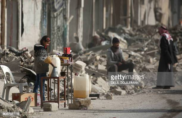 A Syrian girl sells items amidst the debris of destroyed buildings in the northern Syrian city of Raqa on January 11 2018 after a huge military...