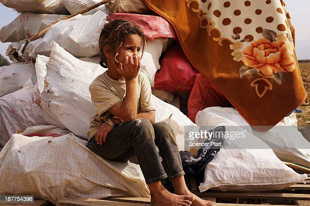 Syrian girl sits on bags of firewood in a makeshift camp for Syrian refugees only miles from the border with Syria in the Bekaa Valley on November 12...