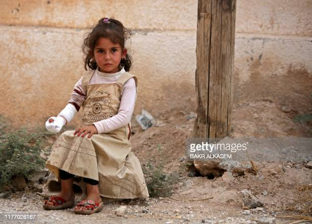 Syrian girl sits on the side of a road after receiving treatment on October 20 in the Syrian border town of Tal Abyad which was seized by...