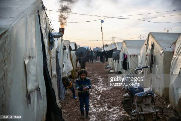 A Syrian girl stands in the mud outside a tent next to a motorcycle at a camp for the displaced near the village of Shamarin near the border with...