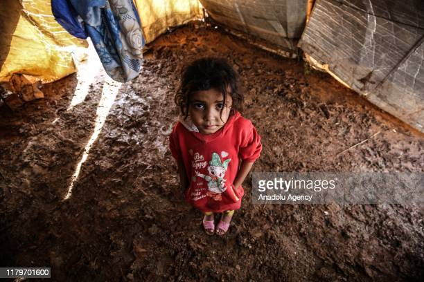 Syrian girl stands on the mud covered road between tents at the Kefernahum refugee camp, where Syrian refugees live, after heavy rain at the...