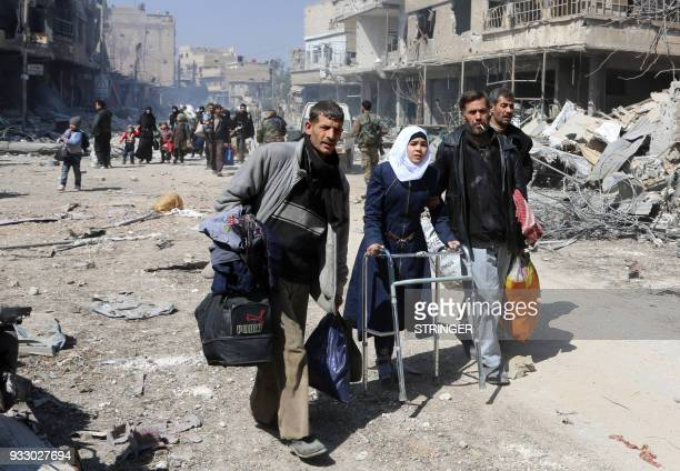 Syrian girl uses a walker as she evacuates with other civilians from the town of Jisreen in the southern Eastern Ghouta on the eastern outskirts of...
