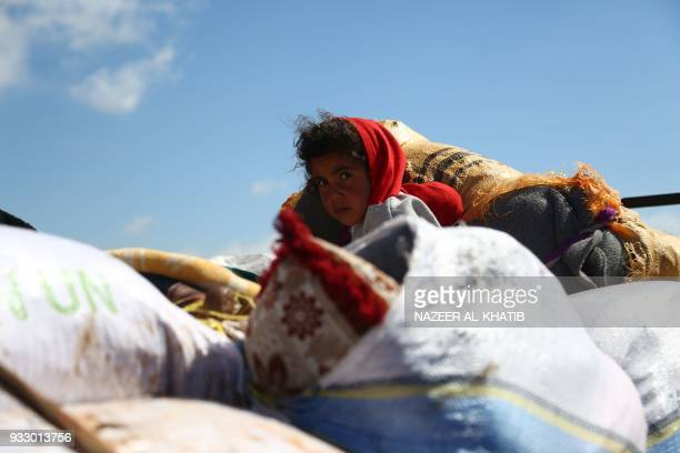 Syrian girl waits at a check point in the village of Anab ahead of crossing to the Turkishbacked Syrian rebels side on March 17 as civilians flee the...