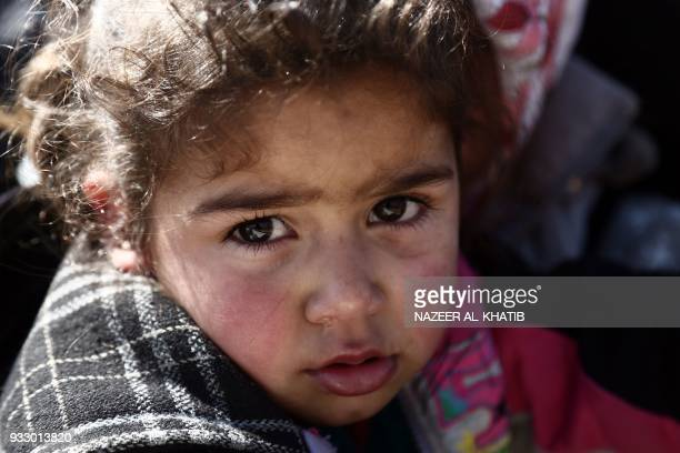 A Syrian girl waits at a check point in the village of Anab ahead of crossing to the Turkishbacked Syrian rebels side on March 17 as civilians flee...