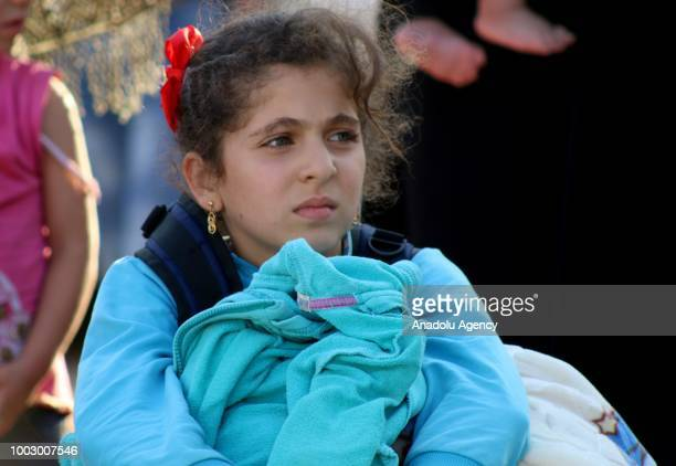 Syrian girl waits to get on a bus headed towards temporary refugee centers in Idlib following the arrival of first evacuation convoy of 40 buses...