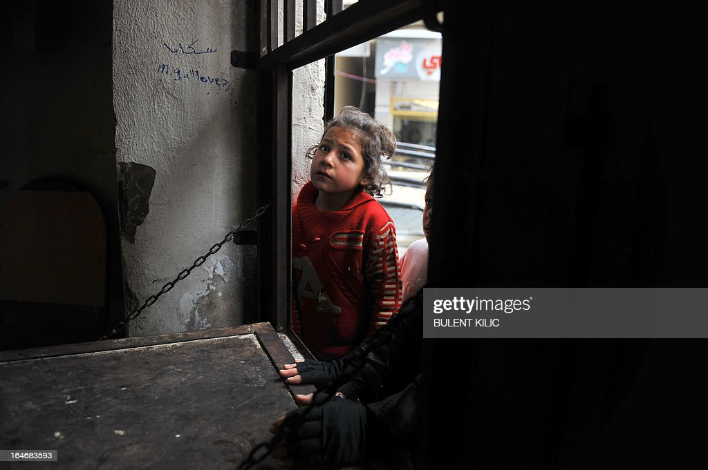A Syrian girl waits to receive food aid in the Bustan al-Qasr district of the northern city of Aleppo on March 26, 2013. Rebels won Syria's long-vacant seat at the Arab League during the organisation's annual summit in Doha, despite rifts within the opposition that have marred their political gains.
