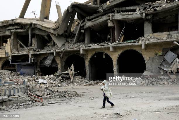Syrian girl walks along a destroyed street in Raqa on December 20 two months after YPG-led Syrian Democratic Forces captured the city from the...