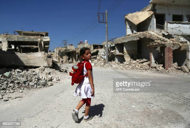 Syrian girl walks down a destroyed street as she heads to school in the rebel-held eastern Ghouta town of Douma on September 20, 2017. / AFP PHOTO /...