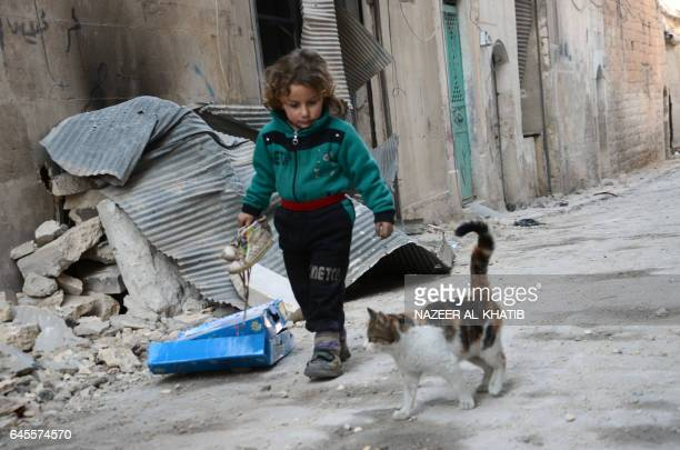 A Syrian girl walks next to a cat in the northwestern Syrian border town of alBab on February 25 2017 after Turkishbacked rebels announced the...