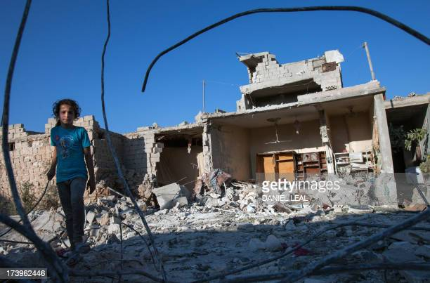 A Syrian girl walks next to the debris of her house after it was targeted by a missile in the northwestern Syrian province of Idlib on July 18 2013...