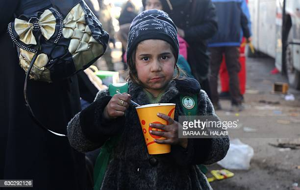 Syrian girl who was evacuated from the last rebelheld pockets of Syria's northen city of Aleppo eats upon arriving on December 20 2016 in the...