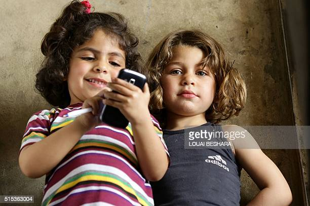 Syrian girls play with a mobile phone at a mechanic shop where their older male siblings work and live with the rest of their family members in the...