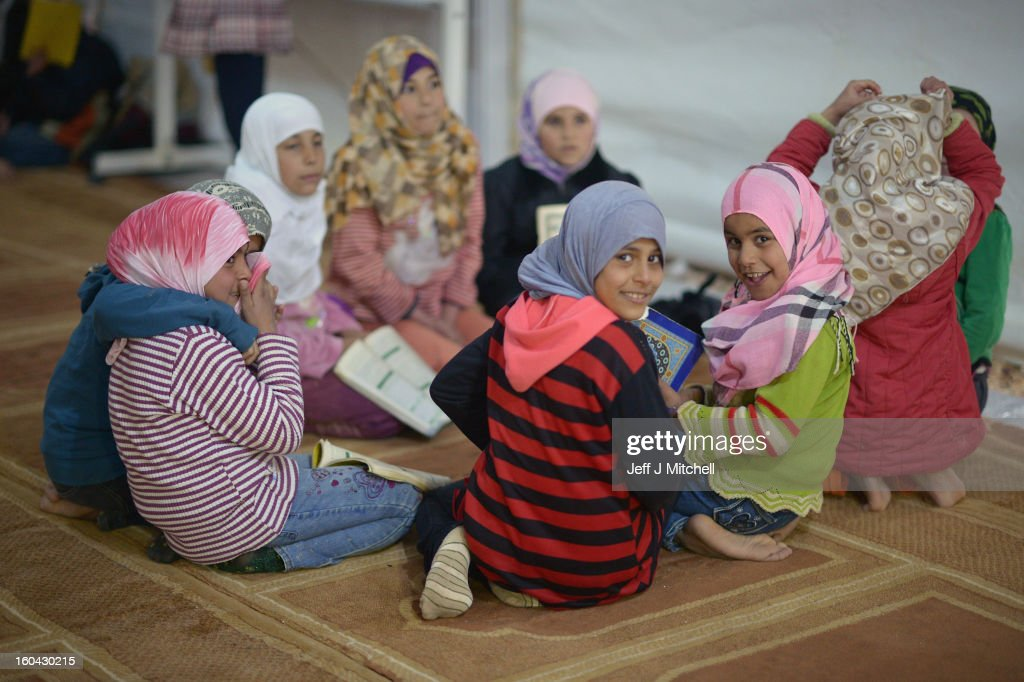 ZA'ATARI, JORDAN - JANUARY 31: Syrian girls read books at a school class held inside a Mosque in the Za'atari refugee camp on January 31, 2013 in Za'atari, Jordan. Record numbers of refugees are fleeing the violence and bombings in Syria to cross the borders to safety in northern Jordan and overwhelming the Za'atari camp. The Jordanian government are appealing for help with the influx of refugees as they struggle to cope with the sheer numbers arriving in the country.